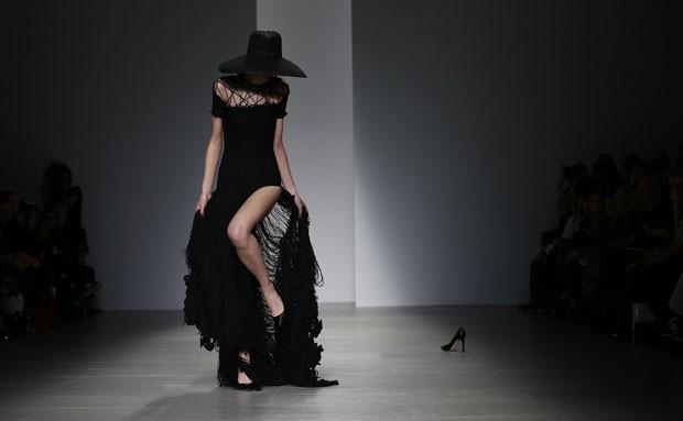 Uma modelo prendeu seu sapato de salto alto no vestido durante desfile outono/inverno na Semana de Moda de Londres, na Inglaterra, no mês passado. Ao fundo, aparece sapato de outra modelo após incidente semelhante (Foto: Suzanne Plunkett/Reuters)