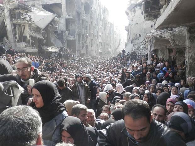 Multidão de moradores do bairro al-Yarmouk, transformado em campo de refugiados no sul de Damasco, aguardam a distribuição de alimentos pela agência UNRWA, da ONU. Os residentes se encontram encurralados no bairro há 8 meses devido à guerra na capital. (Foto: Reuters/UNRWA)