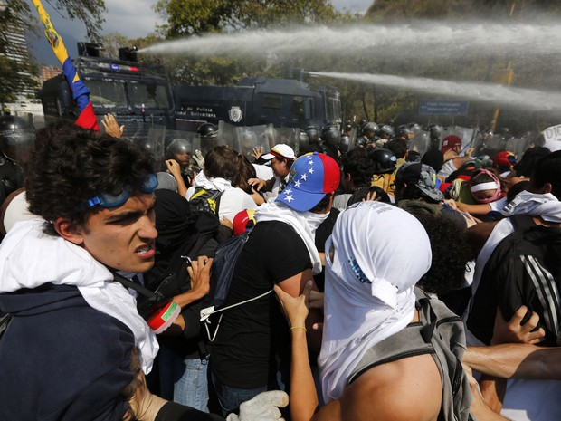 Manifestantes anti-governo são dispersados com canhões de água e gás lacrimogêneo lançado pela polícia durante protesto em Caracas. (Foto: Tomas Bravo)