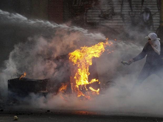 Manifestante tenta atear fogo em uma barricada enquanto policia joga canhão de água durante confrontos em Caracas (Foto: Christian Veron/Reuters)