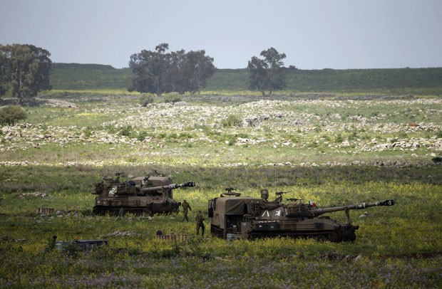 Soldados de Israel andam ao lado de unidades móveis de artilharia perto da cidade de Katzrin, nas Colinas de Golã, nesta quarta-feira (19). Israel atacou alvos sírios. (Foto: Ronen Zvulun/Reuters)