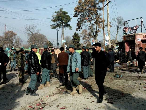 Policiais afegãos e civis inspecionam o local de um ataque suicida no Afeganistão. (Foto: AP Photo)