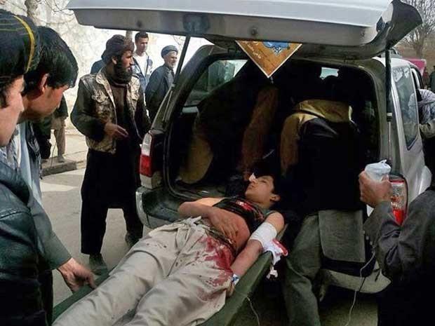 Afegãos ajudam no resgate de um ferido. (Foto: AP Photo)