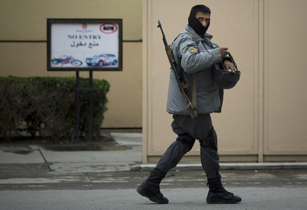 Policial afegão guarda a entrada do hotel Serena em Cabul, no Afeganistão, nesta sexta-feira (21). Homens armados invadiram o local e abriram fogo, matando pelo menos nove pessoas (Foto: Anja Niedringhaus/AP)
