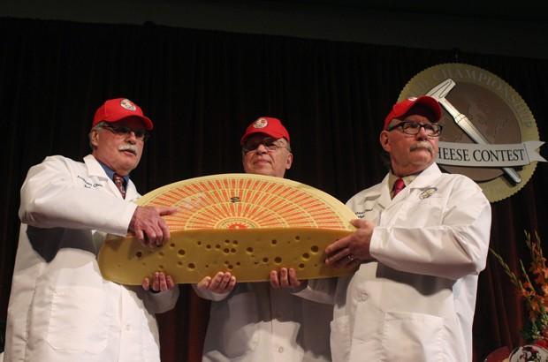 Juízes exibem queijo emmetanler, produzido na Suíça, que levou o primeiro lugar no Campeonato Mundial de Queijo (Foto: Carrie Antlfinger/AP)
