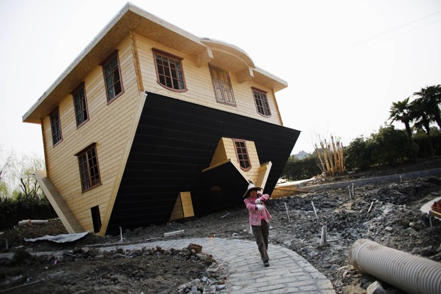 Operária faz pausa durante construção de casa de ponta cabeça da China (Foto: Carlos Barria/Reuters)