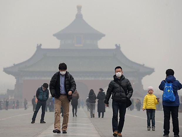 Visitantes usam máscaras enquanto visitam o Templo do Céu, em Pequim. (Foto: China Out/AFP)
