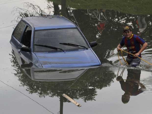 Homem tenta retirar um carro de uma rua inundada após chuvas pesadas em Cali. (Foto: Jaime Saldarriaga / Reuters)