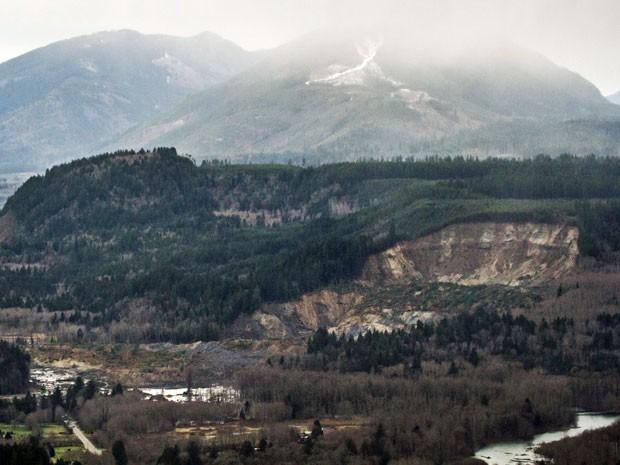 Vista aérea mostra os danos do deslizamento após ser retirado um pedaço de terra do lado da colina de frente ao Rio de Stillaguamish (Foto: AP/ Marcus Yam/ The Seattle Times)
