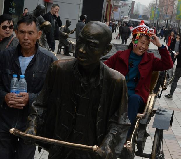 Mulher sorri ao posar em riquexó 'puxado' por estátua na rua comercial de Wangfujing em Pequim, na China (Foto: Mark Ralston/AFP)