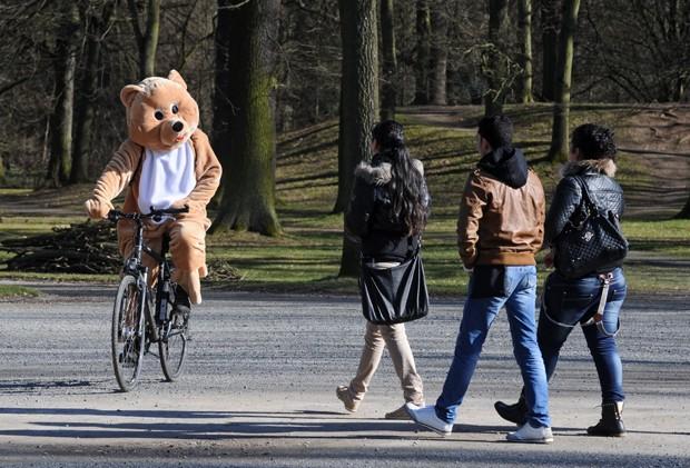 Com roupa de urso, jovem anda de bicicleta a caminho de loja de fantasias na Alemanha (Foto: Uwe Zucchi, DPA/AFP)