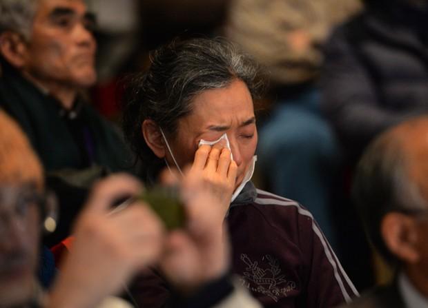 Mulher chora ao ouvir discurso sobre a falta de punição pelo desastre de Fukushima. (Foto: AFP Photo/Yoshikazu Tsuno)