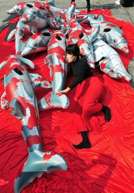 Ativista protesta em meio a bonecos de golfinho de plástico que foram pintados com tinta vermelha, representando sangue derramado pelos animais, vítimas da pesca predatória no Japão (Foto: Jung Yeon-Je)
