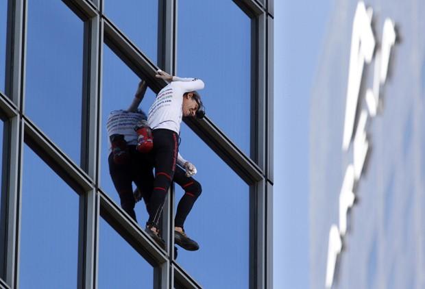 Sem equipamentos de segurança, Alain Robert subiu 48 andares pela fachada, de forma circular (Foto: François Guillot/AFP)