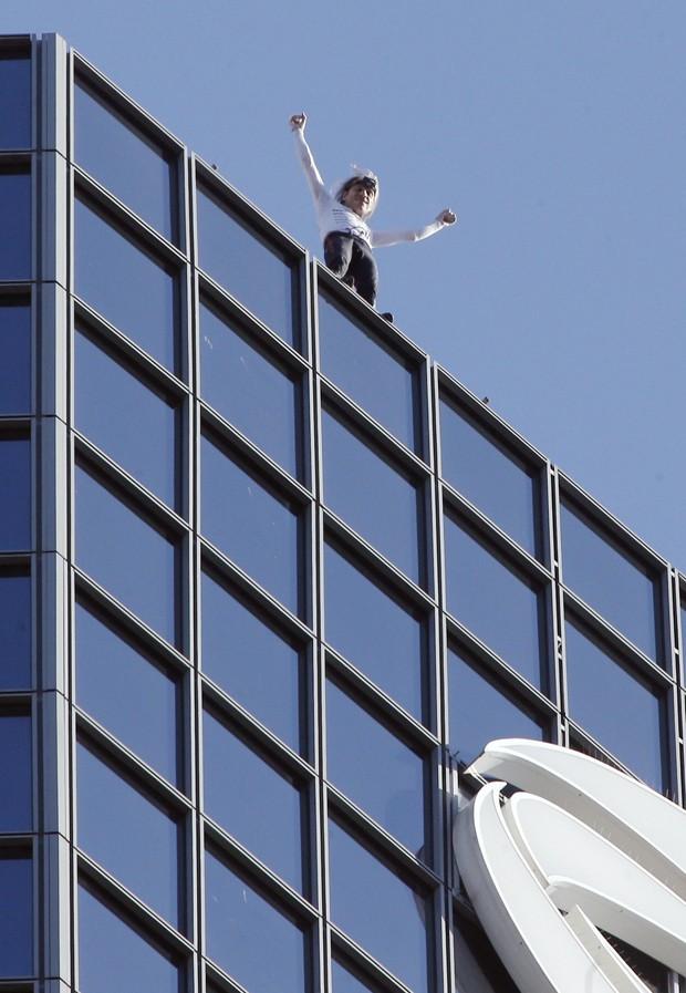 Alain Robert acena do topo de prédio de 186 m em Paris, na França, antes de ser escoltado até a saída por policiais (Foto: François Guillot/AFP)