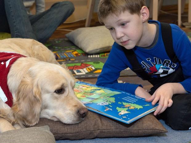 Kevin, de 5 anos, lê para um cão em uma biblioteca da Estônia (Foto: Raigo Pajula/ AFP)