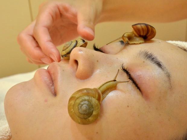 Caracois rastejam no rosto de mulher para demonstrar o novo tratamento de um salão japonês (Foto: AFP)