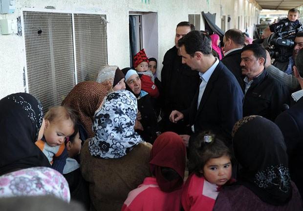 O presidente da Síria, Bashar al-Assad conversa com deslocados no refúgio de al-Duair em Adra, uma província de Damasco situada ao nordeste da capital (Foto: AP)