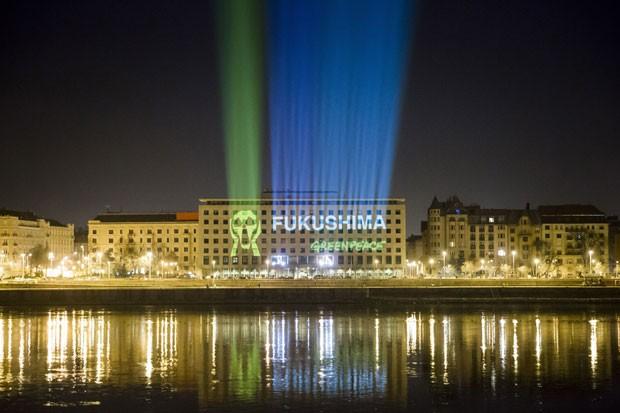 Organização Greenpeace projeta nome Fukushima e logomarca que representa o uso de energia nuclear no prédio do Parlamento húngaro, em Budapeste (Foto: MTI, Balazs Mohai/AP)
