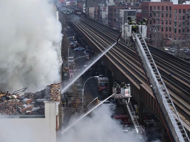 Bombeiros trabalham controlando o fogo ao lado dos trilhos do metrô sobre a Park Avenue, em Nova York (Foto: John Minchillo/AP)