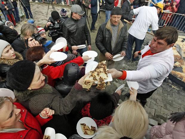 Pessoas pegam pedaços da panqueca gigante na cidade russa chamada Stavropol (Foto: Eduard Korniyenko/ Reuters)