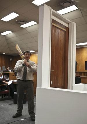 O investigador forense Gerhard Vermeulen mostra como a porta do banheiro da casa de Oscar Pistorius pode ter sido golpeada, durante julgamento do atleta na África do Sul (Foto: Alexander Joe/AP)