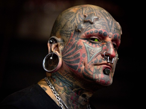 Victor Peralta exibe seu rosto tatuado na feira (Foto: Natacha Pisarenko/AP)