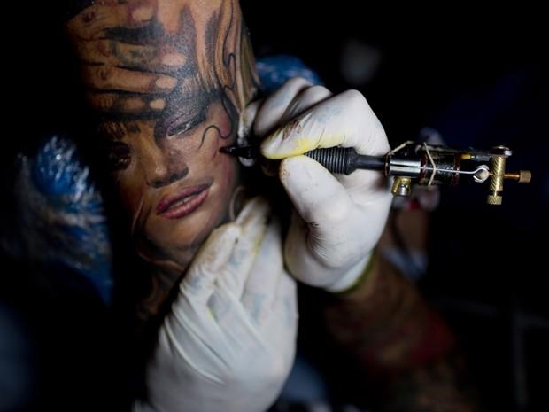 Tatuador Lisandro Libaak tatua uma mulher no braço de Gaspar Obregon (Foto: Natacha Pisarenko/AP)