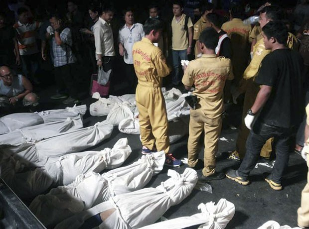 Tailandeses são vistos ao redor de corpos de vítimas de acidente de trânsito no norte do país (Foto: Wichai Taprieu/AP)
