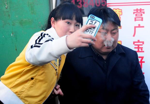 Mulher faz 'selfie' ao lado de vendedor de churrasco na China (Foto: STR/AFP)