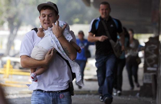 Homem corre protegendo bebê de bombas de gás e pedras durante protestos nesta quinta-feira (6), em Caracas (Foto: Carlos Garcia Rawlins/Reuters)