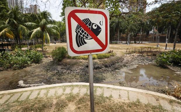 Placa de proibido pescar foi vista diante de viveiro de peixes seco em parque em Cingapura. Em fevereiro, país viveu mês mais seco desde 1869 (Foto: Tim Wimborne/Reuters)