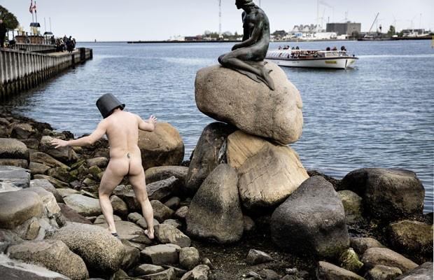 Uwe Max Jensen ficou nu com um balde na cabeça em frente à estátua da Pequena Sereia em Copenhague (Foto: Thomas Lekfeldt/Scanpix Denmark/AP)