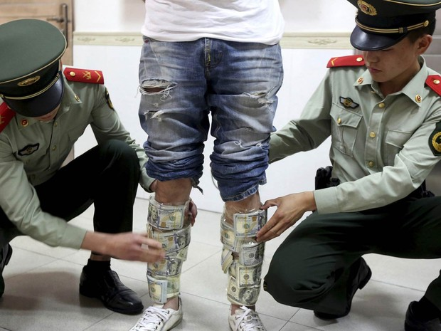 Policiais paramilitares removem maços que somam US$ 580 milhões presos às canelas de um homem detido na fronteira de Hong Kong com Shenzhen, na China. O homem tentava traficar a fortuna para dentro da Região Administrativa Especial de Hong Kong (Foto: Reuters/China Daily)