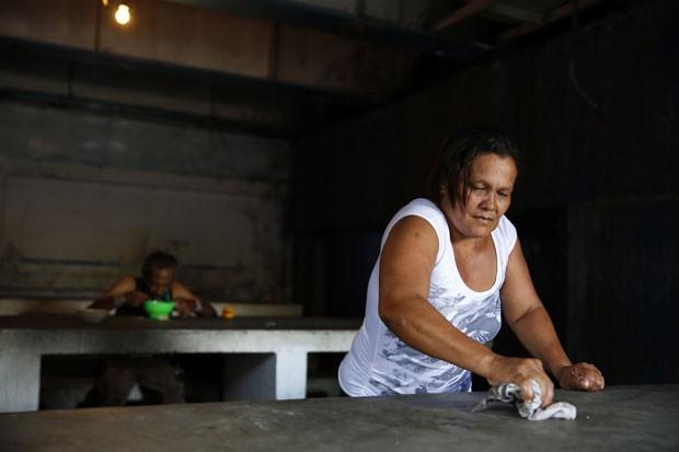 """Fernanda Bolívar, de 54 anos, que há 11 trabalha no """"sopão"""" Madre Teresa, mantido pela Igreja Católica em um beco do centro de Caracas, limpa mesa no local (Foto: Carlos Garcia Rawlins/Reuters)"""