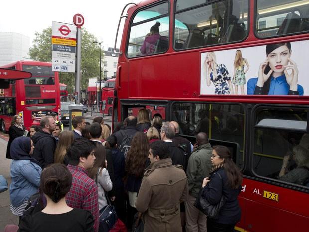 Passageiros tentam entrar em ônibus cheio em Londres nesta terça-feira (29) (Foto: Neil Hall/Reuters)