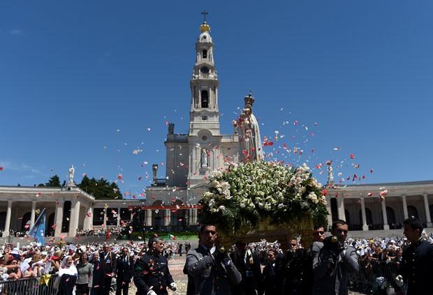 Imagem de Nossa Senhora de Fátima é carregada entre peregrinos em Portugal (Foto: Francisco Leong/AFP)