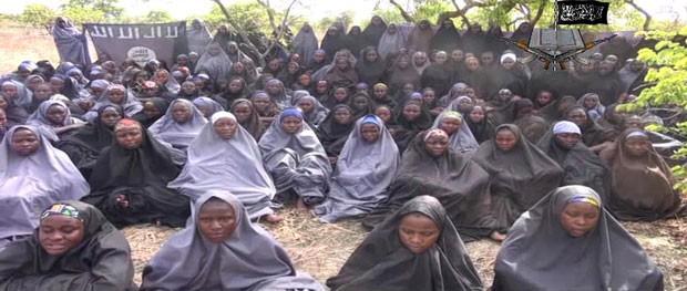Imagem de vídeo divulgado pelo Boko Haram mostra meninas com vestes islâmicas rezando ao ar livre. Jovens seriam as sequestradas em abril na Nigéria (Foto: Boko Haram/AFP)
