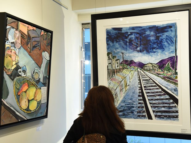 Uma mulher observa as telas 'Still life with peaches' e 'Train tracks, 2013', de Bob Dylan. As obras são parte da mostra 'The drawn blank series', exibida pela galleria Ross Art Group, em Nova York (Foto: AFP Photo/Stan Honda)