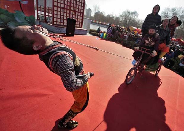 Em 2010, o chinês Yang Guanghe puxou um triciclo carregado com cinco pessoas com ganchos presos em suas pálpebras inferiores durante apresentação em Pequim (Foto: Christina Hu/Reuters)