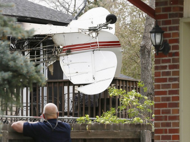 Um avião monomotor puxando uma faixa publicitária caiu em uma casa desocupada no subúrbio de Denver, o piloto não ficou ferido, parte da residência pegou fogo (Foto: Rick Wilking/Reuters)