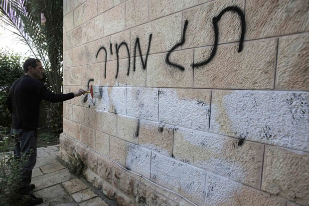 Pichação anticristã é apagada de muro em Jerusalém nesta sexta-feira (9). Inscrição foi feita pouco antes de viagem do Papa Francisco à Terra Santa (Foto: Ammar Awad/Reuters)