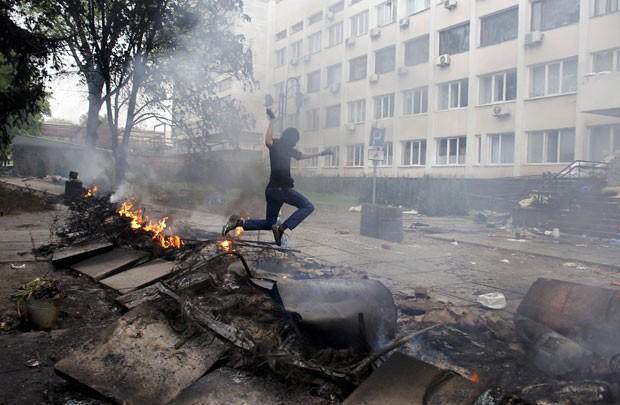 Homem mascarado pula sobre barricada em frente ao prédio da polícia de Mariupol nesta sexta-feira (8). Confrontos deixaram mortos no local (Foto: Marko Djurica/Reuters)