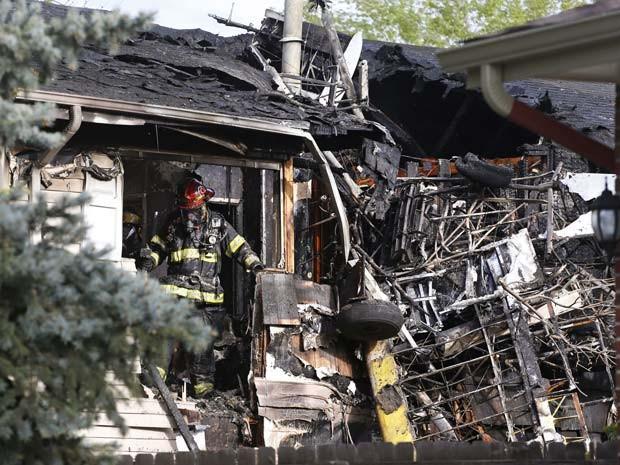 Bombeiro trabalha em escombros de uma casa no subúrbio de Denver, depois de apagar incêndio causado pela queda de um pequeno avião (Foto: AP/Brennan Linsley)
