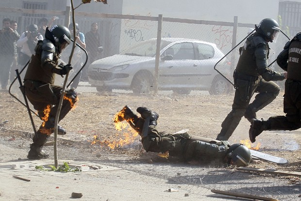 Policial cai em cima de fogo causado por bomba caseira (Foto: Luis Hidalgo/AP)