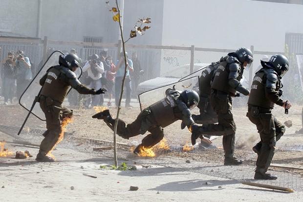 Policial tropeça em um buraco durante protesto de estudantes (Foto: Luis Hidalgo/AP)