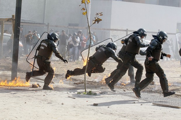 Policial tropeça ao tentar fugir de bomba no Chile (Foto: Luis Hidalgo/AP)