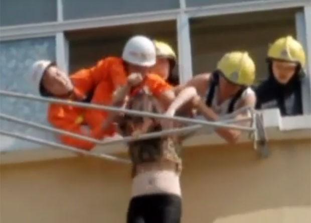 Mulher bêbada foi resgatada após ficar presa em varal na China (Foto: Reprodução/Weibo/cz119)
