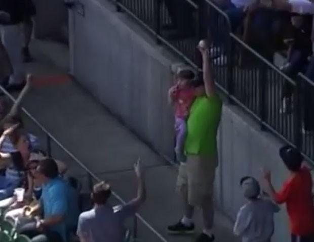 Torcedor conseguiu apanhar bola do jogo enquanto segurava filha no colo em partida de beisebol em Detroit, nos EUA (Foto: Reprodução/YouTube/SportsView)