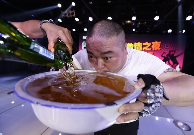 Cantor foi fotografado tentando 'vencer' pote transbordando de cerveja em clube de entretenimento em Pequim, na China (Foto: Jason Lee/Reuters)